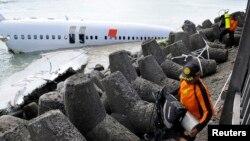 Para anggota tim penyelamat dekat bangkai pesawat Lion Air dekat landasan Bandar Udara Ngurah Rai, Bali, 15 April 2013.