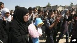 逃離暴力的敘利亞公民沿黎巴嫩和敘利亞邊境,喊口號抗議