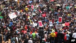 FILE - Hundreds of demonstrators gather at the end of a protest march into Johannesburg, Dec. 16, 2015. The protesters were calling for President Jacob Zuma to be removed.