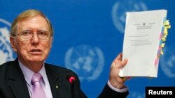 Michael Kirby, Chairperson of the Commission of Inquiry on Human Rights in North Korea holds a copy of his report during a news conference at the United Nations in Geneva on February 17, 2014.