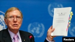 FILE - Michael Kirby, Chairperson of the Commission of Inquiry on Human Rights in North Korea holds a copy of his report during a news conference at the United Nations in Geneva February 17, 2014.