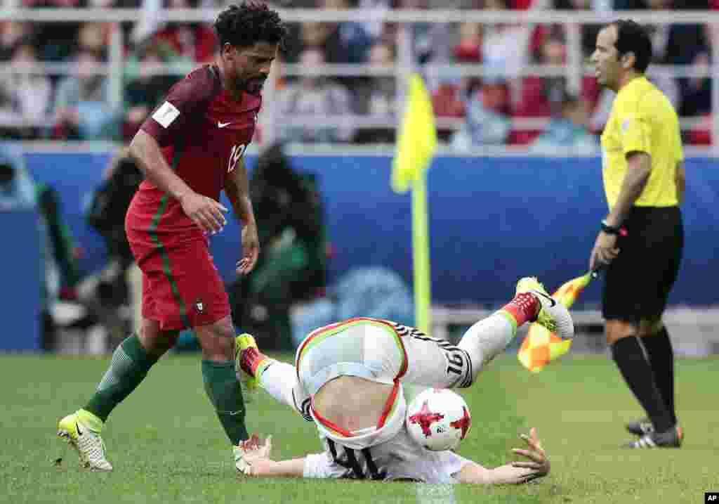 កីឡាករ Eliseu របស់ប័រទុយហ្គាល់ (រូបឆ្វេង) មើលកីឡាករ Hector Herrera របស់ម៉ិកស៊ិក ក្នុងពេលប្រកួតពានរង្វាន់ Confederations Cup នៅក្នុងស្តាត Moscow Spartak ប្រទេសរុស្ស៊ី។