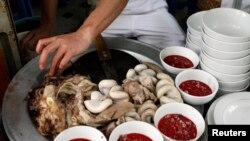 A raw blood dish is displayed with cooked entrails at a restaurant in Hanoi April 28, 2009. Frozen pudding from fresh duck or pig blood is a popular dish in the Southeast Asian country although duck blood is less consumed following bird flu outbreaks that have killed at least 55 Vietnamese since late 2003.