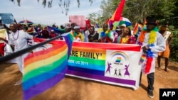 FILE - People holding rainbow flags take part in the Gay Pride parade in Entebbe, Aug. 8, 2015.