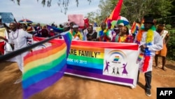 FILE - People holding rainbow flags take part in a Gay Pride parade in Entebbe, Uganda, Aug. 8, 2015. Critics of the new NGO bill say organizations such as those promoting LGBT rights will likely be among those stifled.