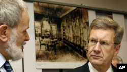 German President Christian Wulff, right, listens to the house director Norbert Kampe, left, during a 70 years 'Wannsee Conference' remembrance day at the house of the Wannsee conference in Berlin, Jan. 20, 2012.