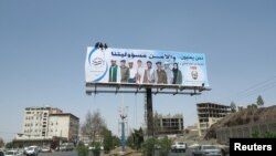 Workers put up a billboard urging citizens to cooperate with security authorities in Sana'a, Yemen, September 30, 2013, the day of the suspected al-Qaida attack on an army base in the eastern city of al-Mukalla.