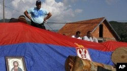 An icon and Serbian flag cover a barricade on the road near the village of Zupce, northern Kosovo, Monday, Aug. 1, 2011