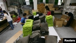 چین کے شہر ڈوانگ گوین میں چینی کارکن برآمد کیلئے ٹی شرٹس پیک کر رہے ہیں