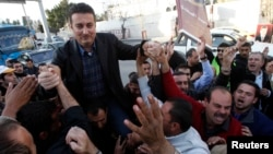 Ahmed Safadi, who won a seat in parliamentary elections, celebrates with his supporters in Amman, Jordan, January 24, 2013.