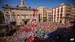 """Anggota """"Castellers"""" Barcelona, kelompok akar rumput yang memimpin gerakan kemerdekaan Catalonia membentuk menara manusia di lapangan Sant Jaume di Barcelona, Spanyol, 24 September 2017. Kelompok itu mengatakan telah mulai membagikan satu juta kartu suara referendum kemerdekaan."""