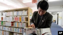 "A ripped copy of Anne Frank's ""Diary of a Young Girl"" picture book is shown by Shinjuku City Library Director Kotaro Fujimaki at the library in Tokyo Friday, Feb. 21, 2014."