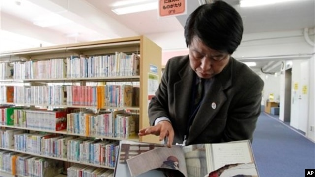 """A ripped copy of Anne Frank's """"Diary of a Young Girl"""" picture book is shown by Shinjuku City Library Director Kotaro Fujimaki at the library in Tokyo Friday, Feb. 21, 2014."""