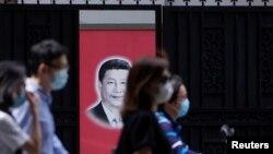 Warga China yang mengenakan masker melewati foto Presiden Xi Jinping di Shanghai (foto: dok). China merilis laporan panjang dan mengklaim kemenangan atas Covid-19 hari Senin (8/6).