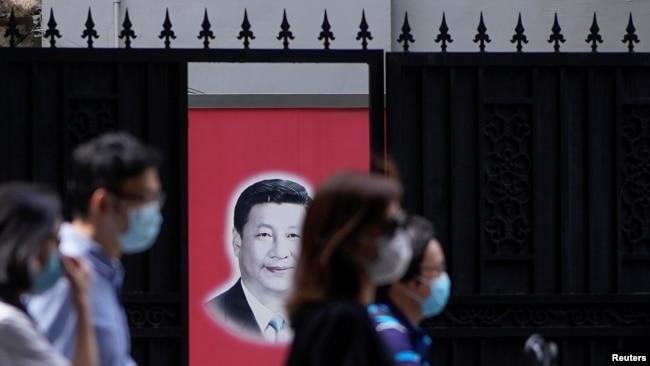 资料照:戴着口罩的上海市民走过内有一幅习近平画像的大门。(2020年5月22日)