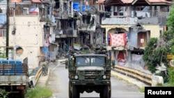 Kendaraan militer pasukan Filipina melakukan patroli melewati kawasan permukiman yang hancur akibat perang di Marawi, Filipina selatan Kamis (19/10).