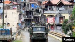 Soldiers on a military truck drive past houses and buildings damaged after government troops cleared the area from pro-Islamic State militant groups inside the war-torn Marawi city, southern Philippines, Oct. 19, 2017.