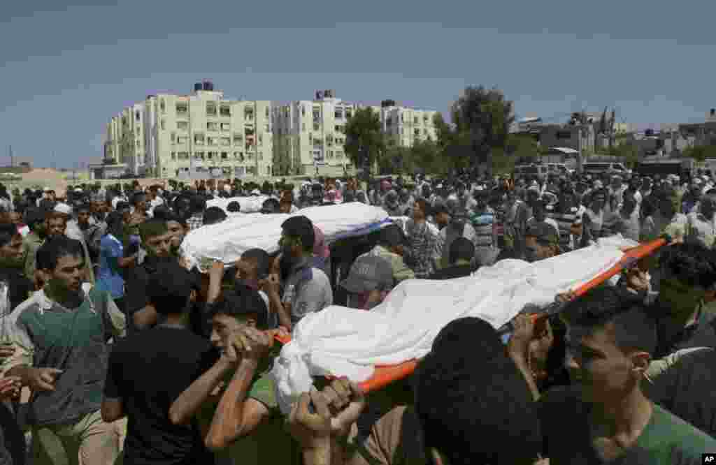 Palestinians carry bodies of 10 members of the Al Astal immediate and extended family that were killed by an Israeli strike on their homes, during their funeral in Khan Younis, southern Gaza Strip, July 30, 2014.