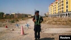 """在新疆伊寧通往一個中國當局稱作""""職業訓練中心""""的再教育營的道路上,一名中國警察在站崗。 (2018年9月4日)"""
