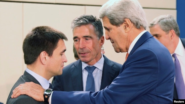 U.S. Secretary of State John Kerry, right, addresses Ukraine Foreign Minister Pavlo Klimkin, left, as NATO Secretary General Anders Fogh Rasmussen listens at a NATO meeting in Brussels June 25, 2014.
