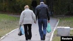 Một cặp vợ chồng già đi bộ trong công viên ở Buenos Aires.
