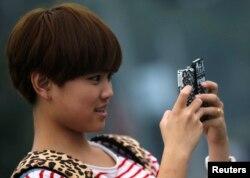 Seorang remaja perempuan memegang dua ponsel saat berfoto di pusat kota Shanghai, 22 Oktober 2012.
