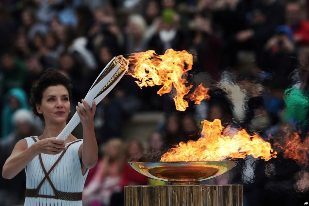 그리스 아테네의 파나티니이코 경기장에서 열린 평창 동계올림픽 성화 전달식에서 여사제 복장의 여배우 카트리나 레호우가 성화봉에 불을 붙이고 있다.