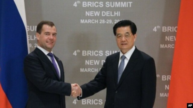 Russia's President Dmitry Medvedev (L) shakes hands with his Chinese counterpart Hu Jintao during their bilateral meeting in New Delhi, March 28, 2012.