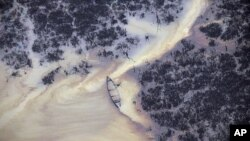 Oil is seen on the creek water's surface near an illegal oil refinery in Ogoniland, outside Port Harcourt, in Nigeria's Delta region, March 24, 2011 (file photo)