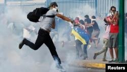 Cảnh sát chống bạo động đụng độ với những người biểu tình ném gạch đá tại Caracas, ngày 19/2/2014.