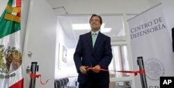 Mexican Consul General Jose Antonio Zabalgoitia cuts a ribbon at the opening of a legal defense center in Miami.