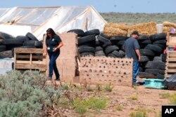 Funcionarios del Departamento de Planeación del Condado de Taos, Rachel Romero, izquierda, y Eric Montoya inspeccionaron las condiciones de propiedad en un desvencijado complejo residencial en Amalia, N.M., el martes 7 de agosto de 2018.