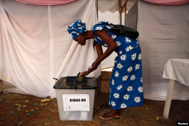 FILE - A woman voter casts her ballot during Rwanda's presidential election, in Kigali, Aug. 9, 2010.
