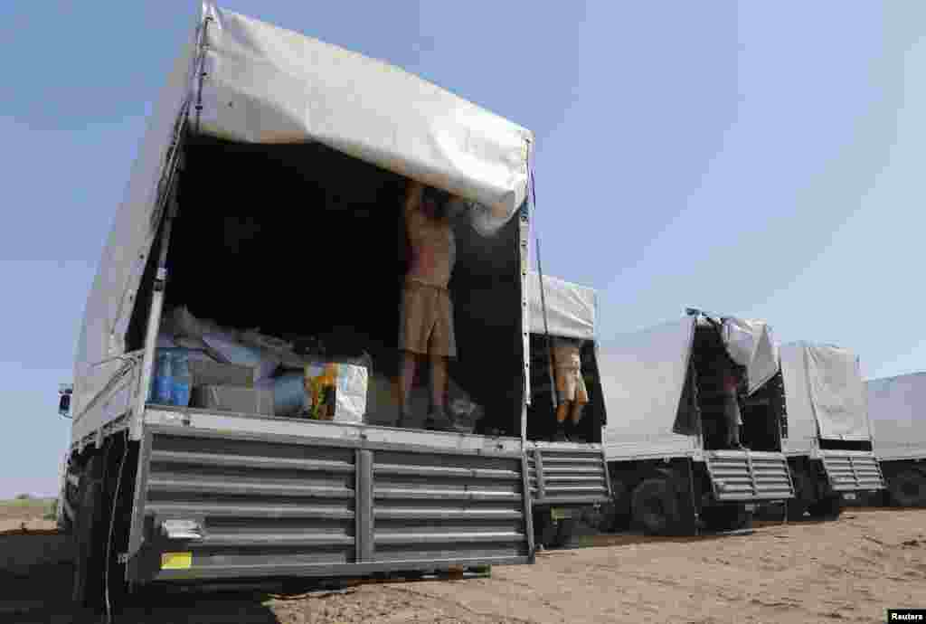 Drivers of a Russian convoy of trucks carrying humanitarian aid for Ukraine open the trucks for inspection at a camp near Kamensk-Shakhtinsky, Rostov Region, Aug. 15, 2014.