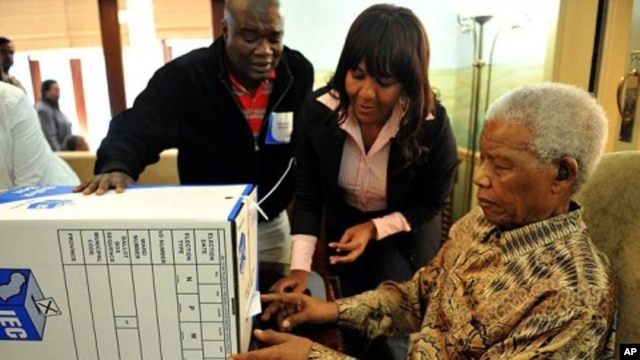 Former president Nelson Mandela, assisted by his grand daughter Ndileka Mandela and an IEC official, casts his special vote for the local government elections at his home in Houghton, Johannesburg, May 16, 2011