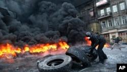 1月25日﹐烏克蘭反政府抗議示威者在基輔市點燃車胎﹐與警察對抗。