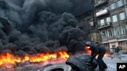 Một người biểu tình chuẩn bị ném 1 lốp xe vào ngọn lửa trong cuộc đụng độ với cảnh sát ở trung tâm Kiev, Ukraina, 25/1/2014