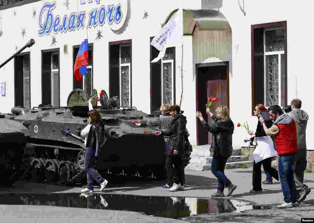 Local residents bring flowers to place them on armored personnel carriers in Slovyansk, Ukraine, April 16, 2014.