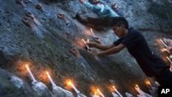 Một người Tây Tạng lưu vong đặt các ngọn nến trên tác phẩm điêu khắc 'Bức tường của Người Tây Tạng Tử Đạo' trong đêm đốt nến cầu nguyện ở Dharamsala, Ấn Độ để tỏ tình đoàn kết với những người Tây Tạng tự thiêu