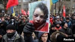 抗議者手舉車娜沃爾的照片。記者車娜沃爾發表有關高層政府官員資產的報道後被毒打。2013年12月26日