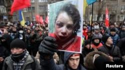Người biểu tình cầm ảnh của nhà báo Tetyana Chornovil bị đánh đập và bỏ trên một cái hào chỉ vài tiếng đồng hồ sau khi bà cho đăng một bài báo nói về tài sản của các viên chức hàng đầu trong chính phủ, 25/12/13