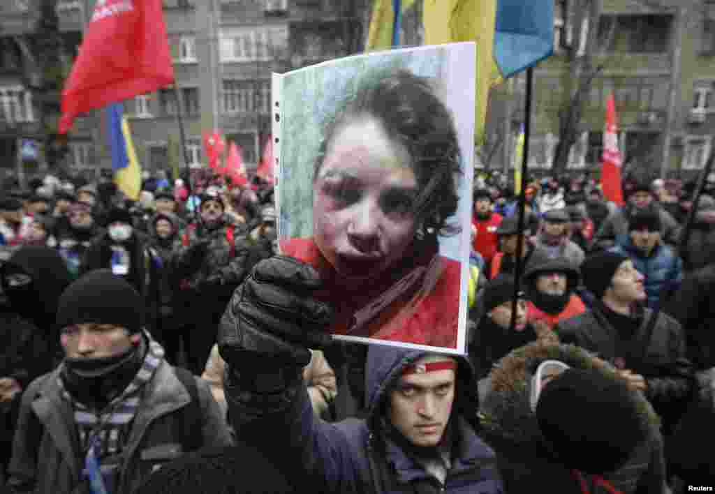 A protester holds a picture of journalist Tetyana Chornovil, who was beaten and left in a ditch just hours after publishing an article on the assets of top government officials, during a protest rally in front of the Ukrainian Ministry of Internal Affairs in Kyiv.
