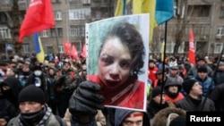 Para pengunjuk rasa Ukraina membawa foto wartawan Tetiana Chornovol dalam demonstrasi mereka di Kiev, 25/12/2013. Chornovol ditemukan dalam keadaan luka-luka di selokan beberapa jam setelah mempublikasikan artikel mengenai aset milik pejabat pemerintah.