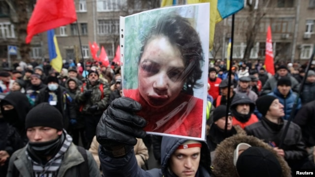 A protester holds a picture of journalist Tetyana Chornovil, who was beaten and left in a ditch just hours after publishing an article on the assets of top government officials, during a protest rally in front of the Ukrainian Ministry of Internal Affairs Internal Affairs in Kyiv, Dec. 25, 2013.