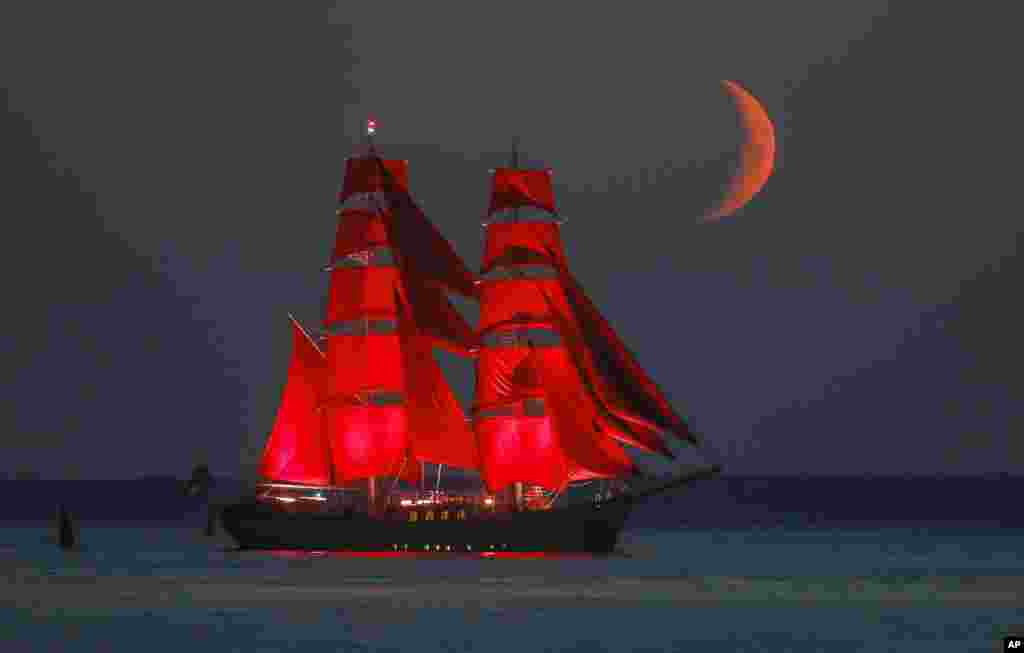 A brig with scarlet sails travels on the Finnish Gulf coast during a rehearsal for the Scarlet Sails festivities marking school graduation which will take place on June 27 in St. Petersburg, Russia, with the setting moon in the background.