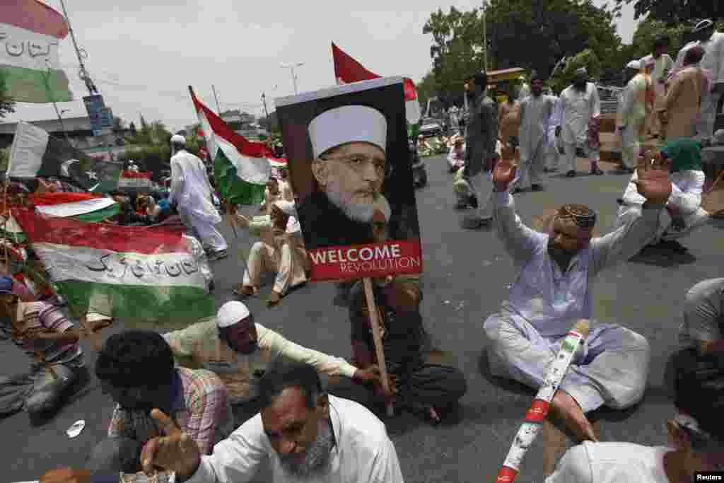 Supporters of cleric Tahir-ul-Qadri chant slogans as they participate in a sit-in protest in Karachi after his plane was diverted from Islamabad to Lahore, June 23, 2014.