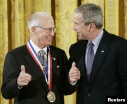 지난 2006년 노먼 볼라그가 조지 W. 부시 전 미국 대통령에게 대통령 훈장인 '자유 메달'을 받고 난 휘 엄지를 치켜들고 있다.