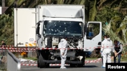 Investigators near the heavy truck that ran into a crowd at high speed, killing 84 people who were celebrating the Bastille Day, July 14 national holiday on the Promenade des Anglais in Nice, France, July 15, 2016.