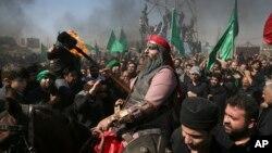 Warga Muslim Syiah Iran merayakan prosesi Ashoura (Asyura) di Teheran, Iran, hari Rabu (12/10).