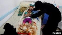 Une femme assiste son enfant souffrant de choléra sur un lit dans un centre de santé à Sanaa, Yémen, 6 juin 2017.